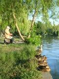Pescador y fila de patos salvajes encendido a orillas del lago Fotos de archivo libres de regalías