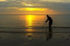 Pescador y fondo de la salida del sol en playa Imagen de archivo libre de regalías