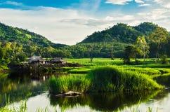 Pescador y montaña del río con sol Imagen de archivo libre de regalías