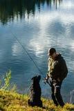 Pescador y perro Fotografía de archivo libre de regalías