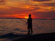 Pescador y puesta del sol Fotografía de archivo