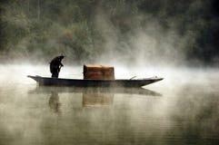 Pescador y su barco por una mañana brumosa fotos de archivo