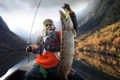 Pescador y trofeo grande Pike imagenes de archivo