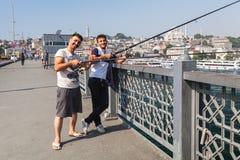 Pescadores adultos jovenes sonrientes en el puente de Galata Foto de archivo