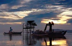 Pescadores asiáticos con puesta del sol. Imagen de archivo