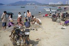 Pescadores chinos y red de clasificación turística rusa con la captura en la playa fotos de archivo