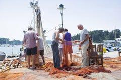 Pescadores con la red de deriva en muelle en Rovinj Foto de archivo libre de regalías