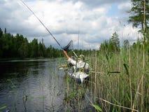 Pescadores con las cañas de pescar en una pesca del barco cerca del río Foto de archivo