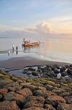 Pescadores de Bali que preparam seu barco no alvorecer na praia de Sanur. Foto de Stock