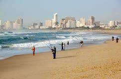 Pescadores de la madrugada en la playa de Durban con los hoteles en Backgroun Foto de archivo