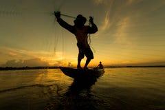Pescadores e crianças que pescam no rio que uma cor dourada mostra em silhueta Imagens de Stock Royalty Free