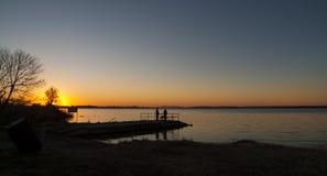 Pescadores em uma doca de madeira no nascer do sol no lago Fotografia de Stock Royalty Free