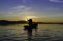 Pescadores en la puesta del sol Foto de archivo libre de regalías