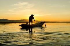 Pescadores en la puesta del sol foto de archivo