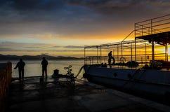 Pescadores en la puesta del sol imagenes de archivo
