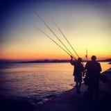 Pescadores en puesta del sol Fotos de archivo