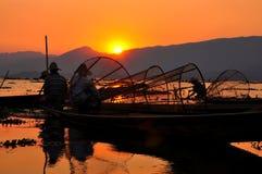 Pescadores en puesta del sol de los lagos Inle. Imagen de archivo