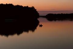 Pescadores en un barco que flota en el lago después de sol Imágenes de archivo libres de regalías