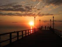 Pescadores en un muelle en la puesta del sol Fotografía de archivo libre de regalías