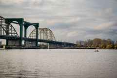 Pescadores en un pescado de cogida del barco inflable en el río en el puente Imagen de archivo
