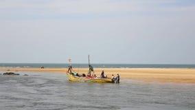 Pescadores indios en un barco grande de Yellow Sea en un fondo de la arena amarilla y del océano azul almacen de metraje de vídeo