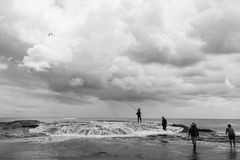 Pescadores na praia de Muriwai imagens de stock