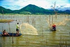 Pescadores na rede de pesca da carcaça do barco para travar peixes no pântano Imagem de Stock Royalty Free