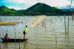 Pescadores na rede de pesca da carcaça do barco para travar peixes no pântano Foto de Stock Royalty Free