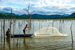 Pescadores na rede de pesca da carcaça do barco para travar peixes no pântano Imagens de Stock