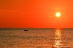 Pescadores no mar pelo por do sol imagens de stock
