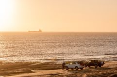 Pescadores no por do sol perto de Long Beach no deserto de Namib fotos de stock
