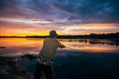 Pescadores pelo rio em um fundo do por do sol imagens de stock royalty free