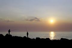 Pescadores por el mar en la puesta del sol Imágenes de archivo libres de regalías