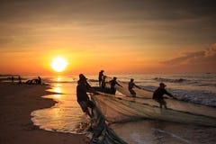 Pescadores que arrastran redes en la salida del sol imagen de archivo