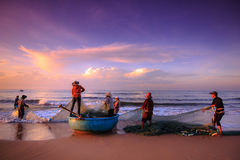 Pescadores que arrastran redes en la salida del sol foto de archivo