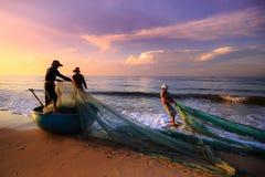 Pescadores que arrastran redes en la salida del sol fotografía de archivo