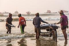 Pescadores que cargan pescados Fotos de archivo