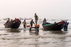 Pescadores que cargan pescados de los barcos rastreadores Imágenes de archivo libres de regalías