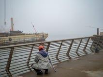 Pescadores que examinan la captura en el embarcadero industrial en día de niebla fotografía de archivo
