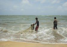 Pescadores que limpian redes Foto de archivo libre de regalías