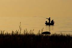 Pescadores que pescam na praia durante no por do sol Fotos de Stock Royalty Free