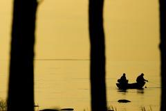 Pescadores que pescam na praia durante no por do sol Fotografia de Stock