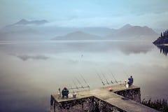 Pescadores que pescan con caña en el lago grande Foto de archivo libre de regalías