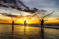 Pescadores que pescan en el mar en la salida del sol Imagenes de archivo