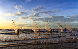 Pescadores que pescan en el mar en la salida del sol Imagen de archivo