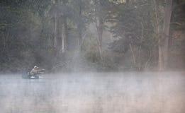 Pescadores que pescan en un lago Imagenes de archivo