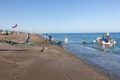 Pescadores que preparan sus redes en la playa Imagen de archivo libre de regalías