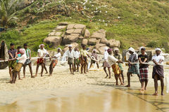 Pescadores que puxam uma rede de pesca do mar árabe Fotos de Stock Royalty Free