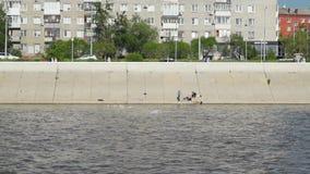 Pescadores que sentam-se na terraplenagem do rio video estoque