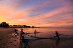 Pescadores que tiran en una red de la playa en la puesta del sol Imagen de archivo libre de regalías